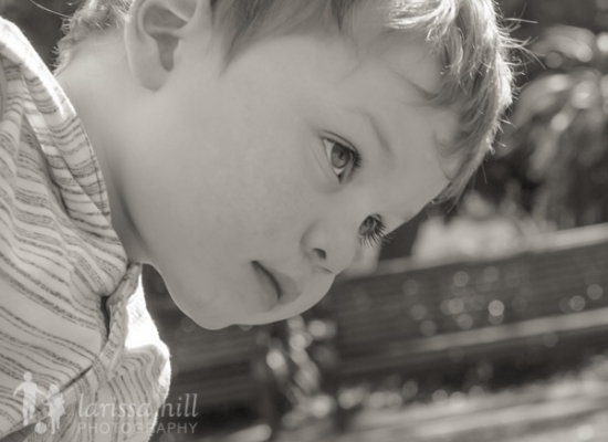 Black and white image of a little boy peering up Larissa Hill Photography Special Needs Kids Photographer