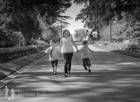 1 girl and 2 boys holding hands and running down a path at Fitzroy Gardens